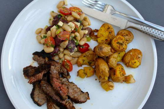 Sliced rib steak, Mediterranean inspired white bean salad and smashed baby potatoes with rosemary